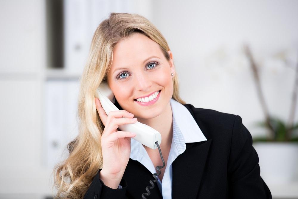 Immobilienmakler - Frau mit telefon für die Maklerberatung